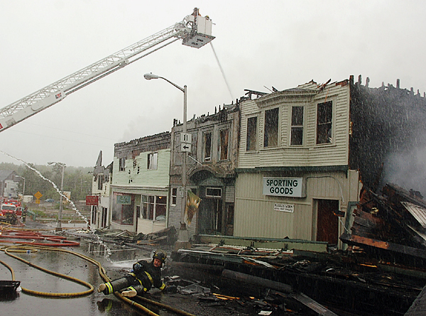 A firefighter is thrown to the ground after losing control of a high-powered hose while fighting the fire that consumed Milo's Main Street in September 2008. Buy Photo
