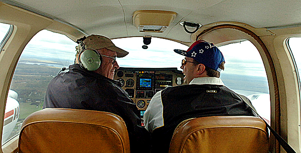 Doug Kell of Ellsworth (left) shares a laugh with Paul Houston of Dedham, a Special Olympian, while flying his 1979 Grumman Cougar for the Penobscot County Special Olympics' annual Fly-In fundraiser Saturday, Oct. 4, 2008. A dozen pilots lent their time and aircraft to raise money for Special Olympians.  Buy Photo