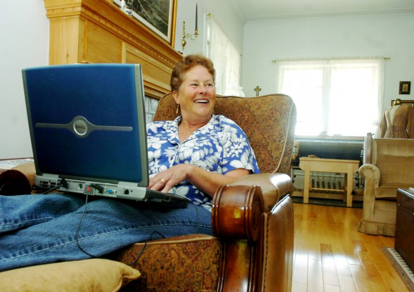 Patty Hill works on her computer in her Eagle Lake home.  The computer, along with everything else which requires electricity in the house, is powered by energy generated by solar panels and wind turbines.  Buy Photo