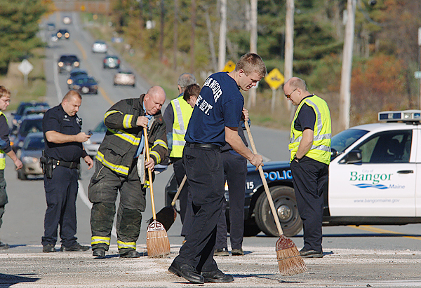 Bangor rescue crews sweep up debris following an accident involving an SUV rear-ending a school bus during the morning of Wednesday, October 8, 2008.  Several victims were transported by ambulance to the hospital. Buy Photo