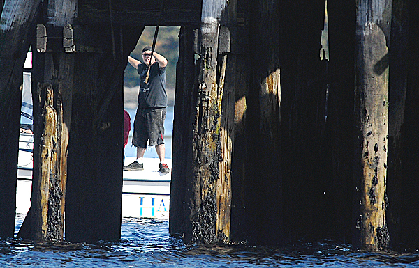 An unidentified volunteer, standing on the edge of a boat, looks between a pilings of a dilapidated pier at Sandy Point Beach early Wednesday afternoon while helping authorities search for an unidentified man who reportedly jumped off the Penobscot Narrows Bridge Tuesday.  Buy Photo