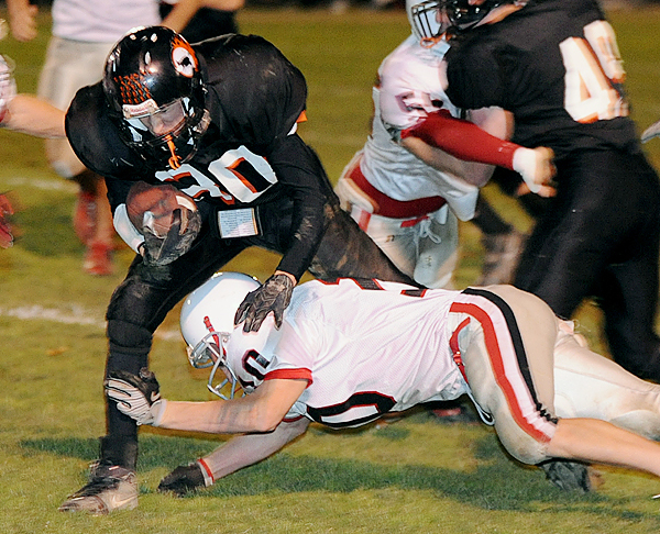 Brewer High School's Billy Bissell (left) scrambles for more yardage as Cony High School'sRick Orio dives to tackle him during the first half of the game in Brewer Friday evening.  Duncklee fumbled on the play and the ball was recovered by Brewer.  Buy Photo