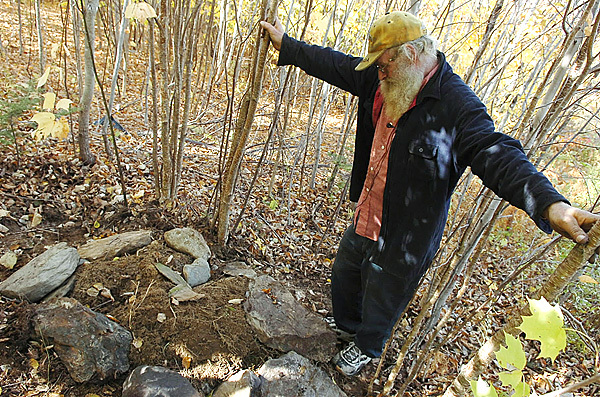 Grafton Burke looks to salvage a few possessions Monday from the ruins of the house he rented on Mill Hill Road in Springfield. A fire Sunday night destroyed the cabin and killed Burke?s dogs. He was not home at the time of the blaze.  Buy Photo