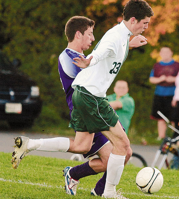 John Bapst HighSchool's Max Cutri (left) and Old Town High School's Casey Clark battle for the ball during the second half of the game in Old Town Monday.  John Bapst won the game 5-0.  Buy Photo