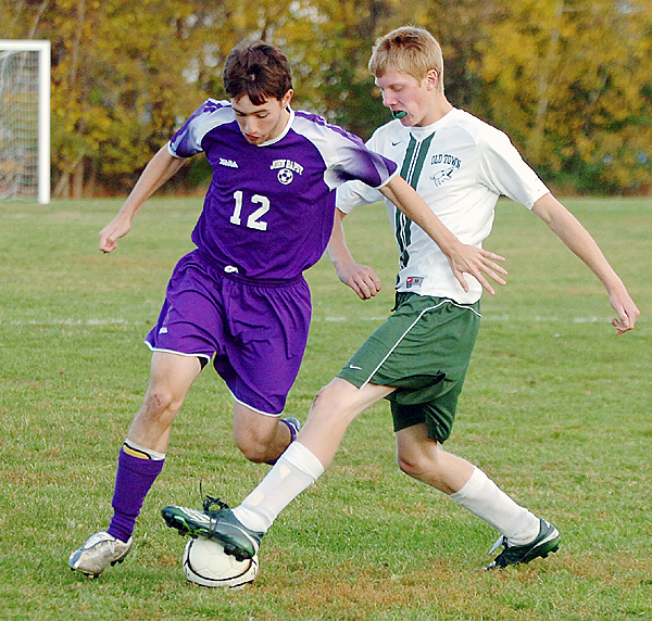 John Bapst HighSchool's Justin Jordan (left) and Old Town High School's Dan Zmistowski battle for the ball during the second half of the game in Old Town Monday.  John Bapst won the game 5-0.  Buy Photo