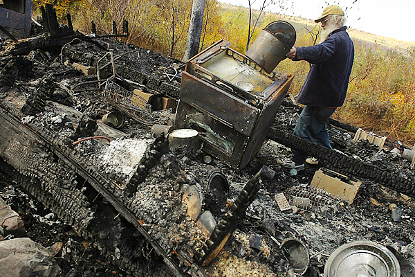Grafton Burke looks to salvage a few possessions from the remains of the rented house he resided in on Mill Hill Road in Springfield on Monday, October 13, 2008.  Although Burke was not home when a fire destroyed the house on Sunday evening, his six dogs perished in the blaze.  Buy Photo