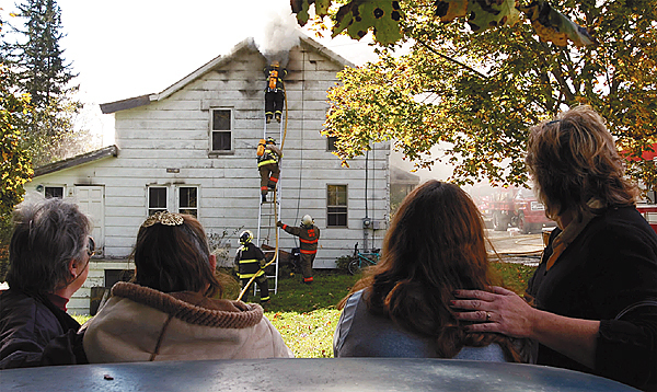 Firefighters from Winterport, Hampden and Frankfort work to extinguish a stubborn fire at 709 Main St. in Winterport around noon Wednesday as homeowner Cindy Hogencamp (second from right) is comforted by her boss, Julie Buzzell (right). Buy Photo