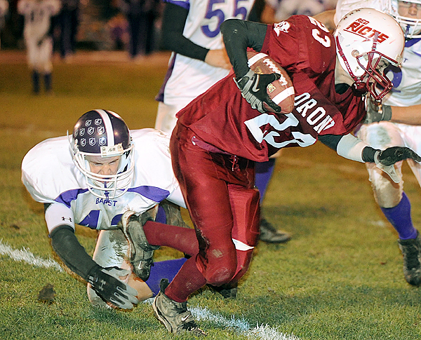 Orono High School's Kirk Francis (right) breakes a tackle by John Bapst High School's Max Andrews during the second quarter of the game in Orono Friday evening.  Buy Photo