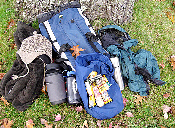 Pack items like these for a safe comfortable fall hike (from left): a fleece hat on top of a fleece insu-lating mid-layer, a water bottle, snacks on top of a stuff sack, a thermos of hot chocolate, a rain shell which doubles as a wind shell. All these items fit inside this small daypack with room for more.