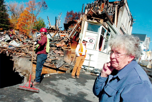 Sandra Haley, lifelong resident of Milo and owner of the Milo Flower Shop, watches as crews tear down the burnt out remains of her business on Friday, October 17, 2008.  Haley owned the business for 36 years before it was destroyed by a deliberately set fire which devastated Milo's Main St. in September.   Buy Photo