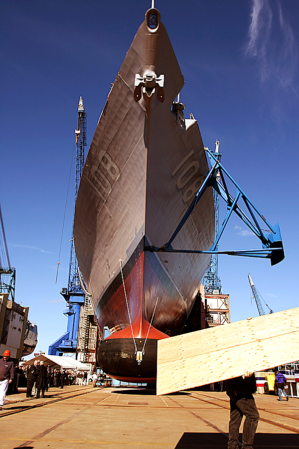 A worker passes in front of the newly-christened Wayne E. Meyer, the 505-foot-long warship docked in the Kennebec River at Bath Iron Works shipyard, in Bath, Maine, on Saturday, Oct. 18, 2008. The retired rear admiral known as the &quotfather of Aegis&quot was the guest of honor as a Navy Aegis destroyer bearing his name was christened. The Meyer represents the 58th destroyer in the class and the 31st built at Bath Iron Works.