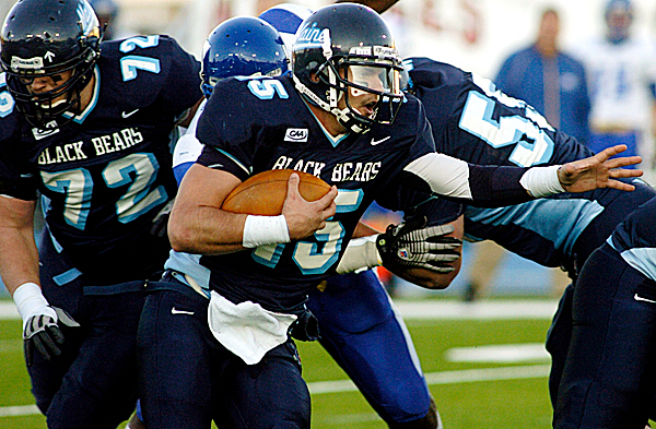 With the help of teammmates Tyler Eastman (#72,left) and Ryan Canary (#55,right) University of Maine quarterback Michael Brusko breaks through the Hofstra line the third quarter of their game at Morse Field at the University of Maine in Orono Saturday afternoon, October 18, 2008.  Buy Photo