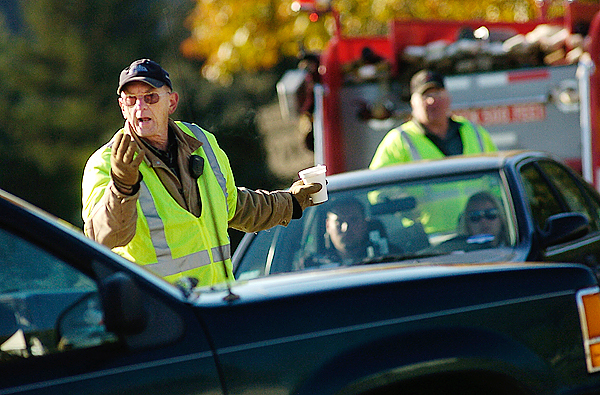 Fire Chief Tim Terry and Lt. El-win Boynton (background) of the Prospect Fire Department redi-rected traffic from a roadblock on Route 1A to Hawes Bridge Road in Prospect while state and local police searched for Randall Ho-fland who remained at large Fri-day morning. Brandishing a fire-arm and making threats to officers, Hofland fled the scene of a routine vehicle safety check on Route 1 in Searsport late Thurs-day night. Buy Photo