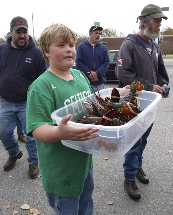 Drew Philip, 11, of Rockland carries a customer's order Saturday for his father, Ryan Post, a lobsterman. Post sold more than 2,000 lobsters - the first 1,000 went in less than an hour - for $3.50 a pound to drum up support for Maine's lobster industry. Buy Photo