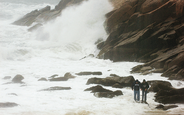 A couple who declined to be identified get caught in the surf on Sunday near Sand Beach in Acadia National Park. High winds brought trees down on wires, causing power outages and snarling traffic on Mount Desert Island during Sunday?s storm. Buy Photo