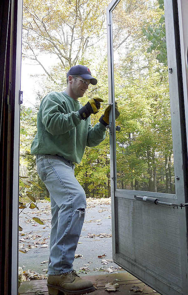Greg Winston of Troy, a Husson University teacher, installs glass in storm doors for Dot Quimby of Unity. Winston was one of dozens of volunteers who winterized 10 homes in the area Saturday, national Make A Difference Day. Winston?s team also installed insulation and foam protectors on exposed pipes. ?How can I say thank you for all this?? Quimby asked. Buy Photo