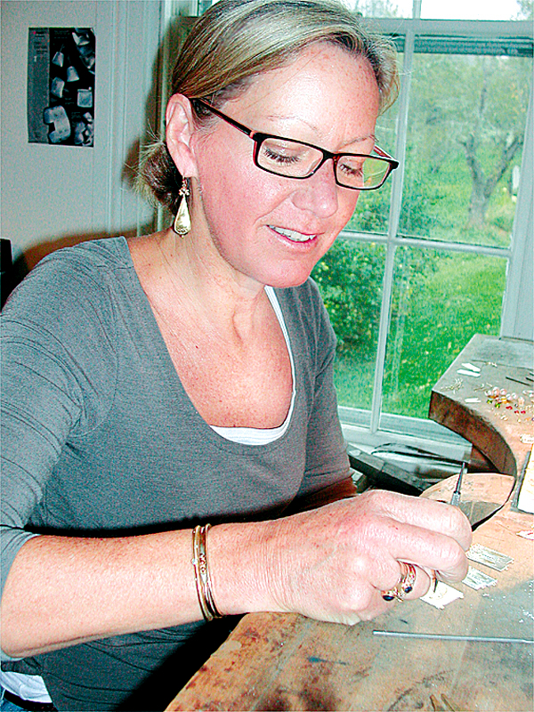 Goldsmith Pamela Hitchcock, in her Winterport studio, works on gold and silver earrings, one of her original jewelry designs.  She began learning her craft as a teenager, a skill she has practiced for over 35 years.  She will be among the artisans displaying and selling handcrafted products at the Designing Women show and sale Saturday, Nov 1, at Husson University