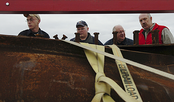 Orrington firefighters (from left) Brian Co-chrane, Greg Spencer and Ron Hamlin and Nickerson & O'Day project manager Walter Shannon (right) take a look Wednesday at steel beams from New York?s World Trade Center that were shipped to their permanent home at the new Brewer Public Safety Building. ?I'm honored and humbled just to bring it back,? said a choked-up Shannon. Buy Photo