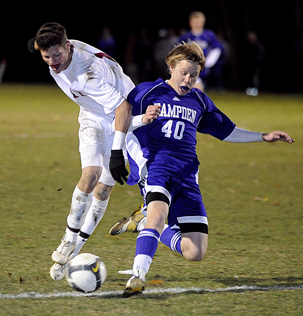 Bangor High School's Johnny Warren( left) and Hampden Academy's Corey Grover battle for the ball during the 1st half of the Eastern Maine Boys Class A quarterfinal game in Bangor Wednesday evening.  Buy Photo