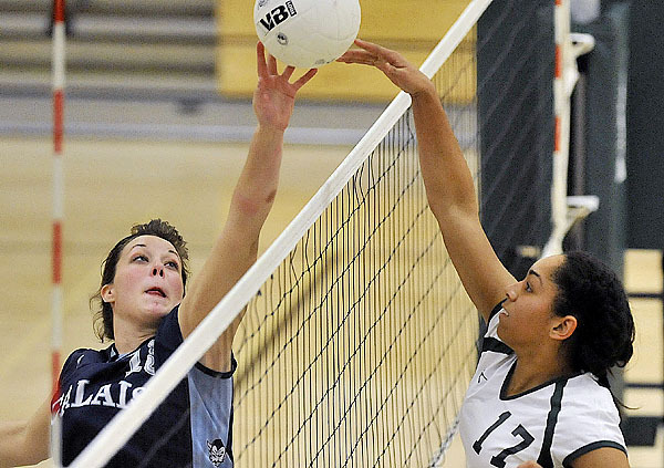 Nicole Osborne of Calais (left) blocks a spike attempt by Mount Desert Island?s Destiny Kanu (17) in the second game of Wednes-day?s Eastern Maine champion-ship match in Bar Harbor. Kanu?s Trojans won the match 25-19, 26-24, 25-19. Buy Photo