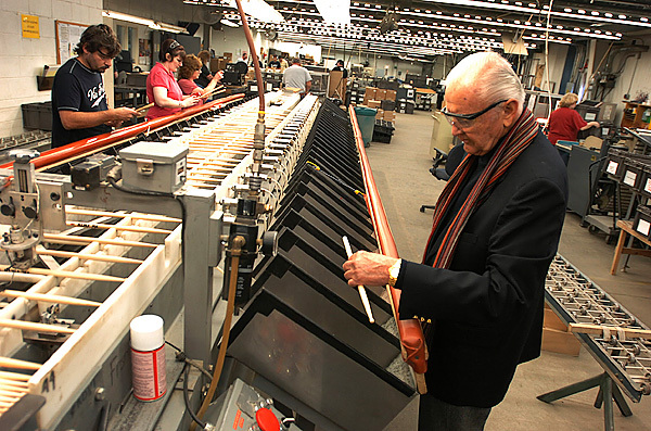 Vic Firth inspects a drumstick as it comes out of a sorting machine at his Newport drumstick-making factory earlier this week in Newport. The machine in front of him strikes the sticks with a tiny hammer as they rotate. The resulting frequency response is used to match similar-resounding sticks to form a matched set.