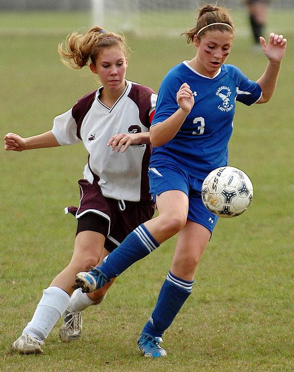 Madawaska's Kallie Pelletier, right,  battles for control of the ball from Orono's Meghan Curtis, left, during first half action at Orono during Wednesday's Eastern Maine final. Orono won 2-1.  Buy Photo