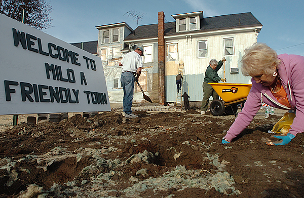 A group of nearly a dozen volunteers including Terry Bouchard (right) plant close to 200 tulip bulbs Wednesday, Nov. 5, 2008 where the Milo True Value Hardware Store once stood before a devastating fire leveled much of the downtown area last September. A sign (left), made by town selectmen chairman Joe  Bares waits to be erected in the empty space where it will be surrounded by pink tulips. It will replace a similar one which had been there as long as anyone could remember, and burned with the store.  Buy Photo