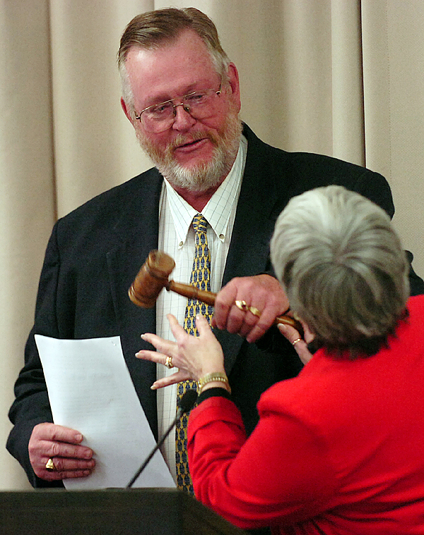 Newly re-elected Bangor City Councilor and newly appointed Bangor City Council Chairperson, Gerry Palmer, left, receives a gavel from out going Bangor City Council Chairperson Susan Hawes on Monday, November 10, 2008 at Bangor City Hall.  Buy Photo