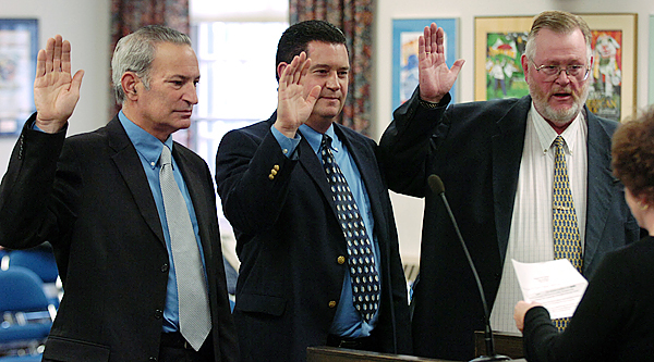 (L to R) Rick Bronson, Daivid Neally, and Gerry Palmer are sworn in as Bangor City Councilors by city clerk, Patti Dubois, far right,  on Monday, November 10, 2008 at Bangor City Hall. Buy Photo
