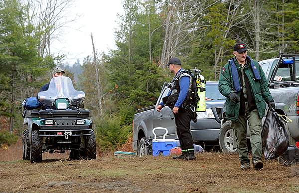 Game wardens and Bowerbank area volunteers bring gear up to the logging road from the shore of First Buttermilk Pond Monday.  Warden Service divers found the body of Robert Pomeroy shortly before 11am .  Maine Warden Service Lt. Pat Dorian said that Pomeroy's body was found in fairly shallow water close to the north shore of the pond.   Buy Photo