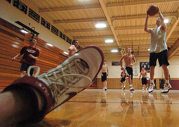 Bangor High School sophomore Tristan Thomas (right) puts up a shot during a scrimmage as the Rams opened preseason tryouts Monday afternoon. Monday marked the first day of preseason tryouts and practices for winter sports teams around the state.