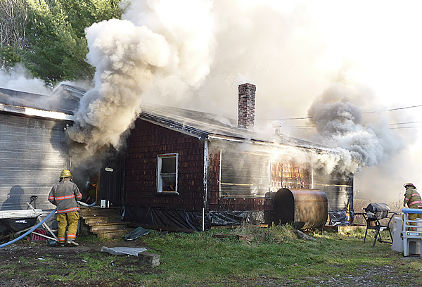 Firefighters from four towns battle a house fire at 27 River Road in Detroit on Monday.