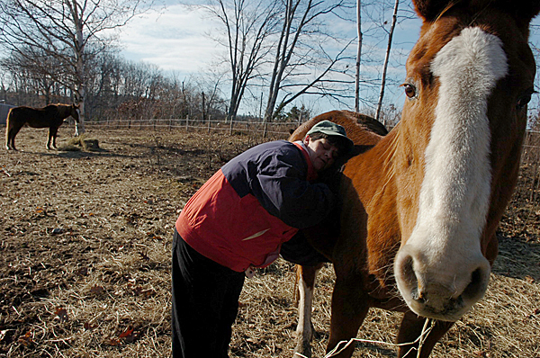 Mary Myshrall, owner of the Last Chance Ranch in Troy, hugs one of the horses she has rescued. Myshrall, who has operated the rescue facility for four years, currently is caring for 14 horses, the ranch's limit. Buy Photo