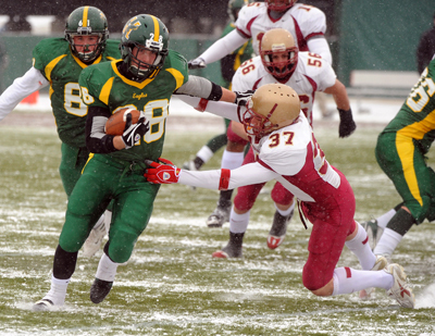 Husson University's Justin Lindie (left) breaks a tackle by St. John Fisher College's  Jason Cirulli during the first quarter of the game in Bangor Saturday.  Buy Photo