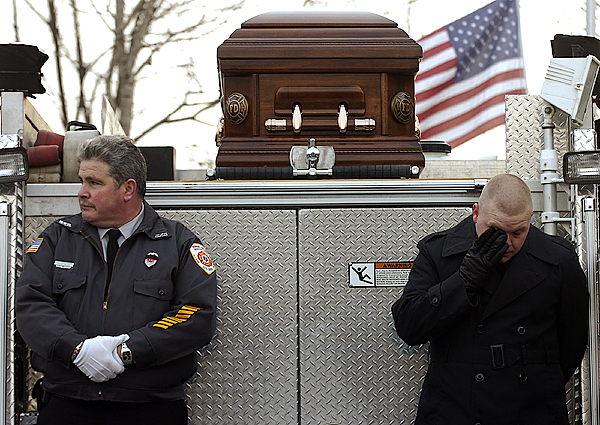 As the Hartland town fire siren moans in the distance, Newport fireman Thomas Snowman, left, brother of fallen fire fighter Michael Snowman looks away, while Canaan fireman Benjamin Snowman, son of Michael Snowman wipes a tear from his eye during the last call ceremony at the Hartland Volunteer Fire Department on Saturday. Buy Photo