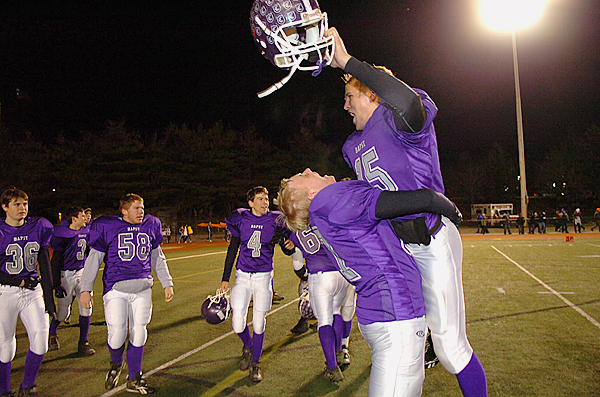 The John Bapst Crusaders, including junior Shane Hass (right) and senior Alan Snapp (holding Hass), celebrate their win over Winthrop 21-14 for the Class C state football championship at Fitzpatrick Stadium in Portland on Saturday. It's the team's first title since 1976.  Buy Photo