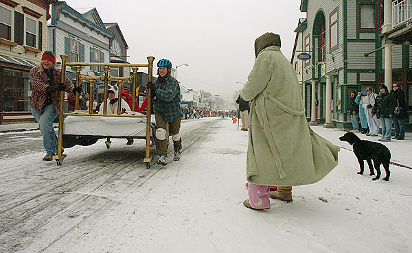 Brass Bedlam bed-racing team members (from left) Natalie Springuel, Lyn Gatz (on bed) and Millie Phemister sprint past Nan Ulett and a dog named Ruby as they slip and slide on a snow-covered Cottage Street in Bar Harbor on Saturday during the Bar Harbor Chamber of Commerce's first Bed Race.  Buy Photo