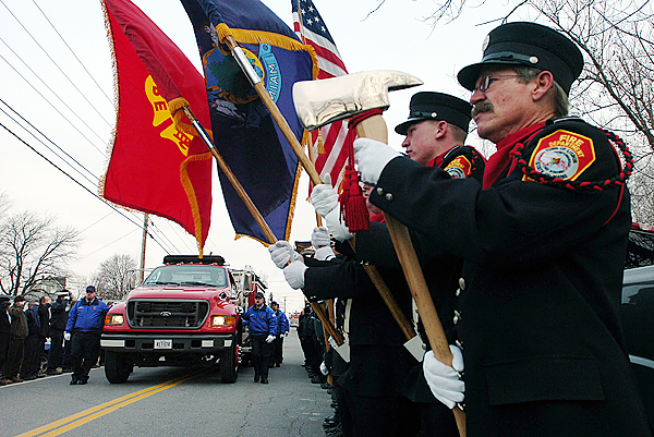 Lisbon Fire Department honor guard member, Tom Wrobel, right stands at attention on Saturday, as the fire engine carrying the body of fallen firefighter Michael Snowman parades past and into the Hartland Fire Department's station for Snowman's last call ceremony.  Buy Photo