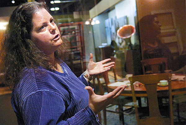 """Laurie LaBar, chief curator of history at the Maine State Museum in Augusta, explains aspects of one of the eight sections of the exhibit, """"Comfort and Sociability,"""" which re-creates a family dining room from 1938 from Bangor. Buy Photo"""