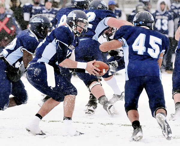 Maine's quarterback Michael Brusko, left, hands off to Jared Turcotte (45) in the second quarter of an NCAA college football game against New Hampshire in Orono, Maine, Saturday, Nov. 22, 2008.