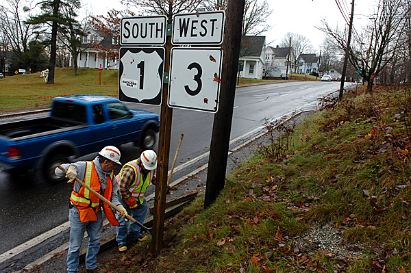 Maine Department of Transportation workers Tom Brenton and Steve Carmean secure a route sign in Ellsworth which had been uprooted by Tuesday night's powerful winds.  Bangor Hydro reported that downed lines left as many as 14,400 customers without power, most of which were located in the hard hit Hancock County.  Buy Photo