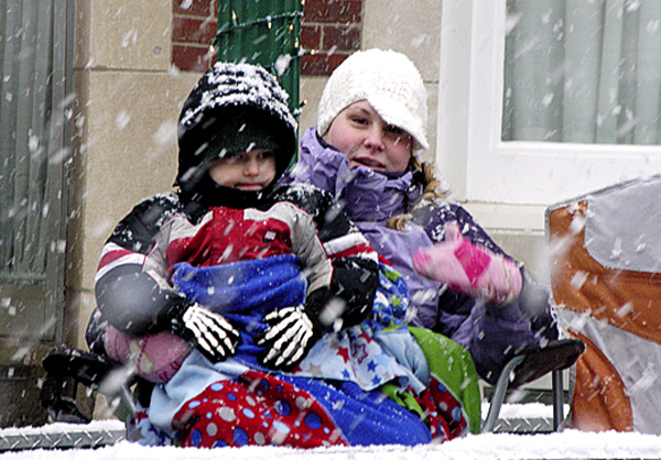 Carolyn Hawkins of Ellsworth and her son, Mason, 3, bundle up against the snowflakes Saturday during the Ellsworth Christmas parade.  Buy Photo