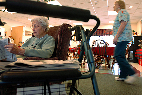 "Betty LeBretton (left) reads the morning paper Monday in the activity room at The Meadows, an assisted living facility in Orono. A new state eligibility rule could force some residents to find new housing. ""The thought of sending some of these people to the hospital and telling them, 'You can't come back' is appalling,"" said Meadows administrator Gerri Viitala. Buy Photo"