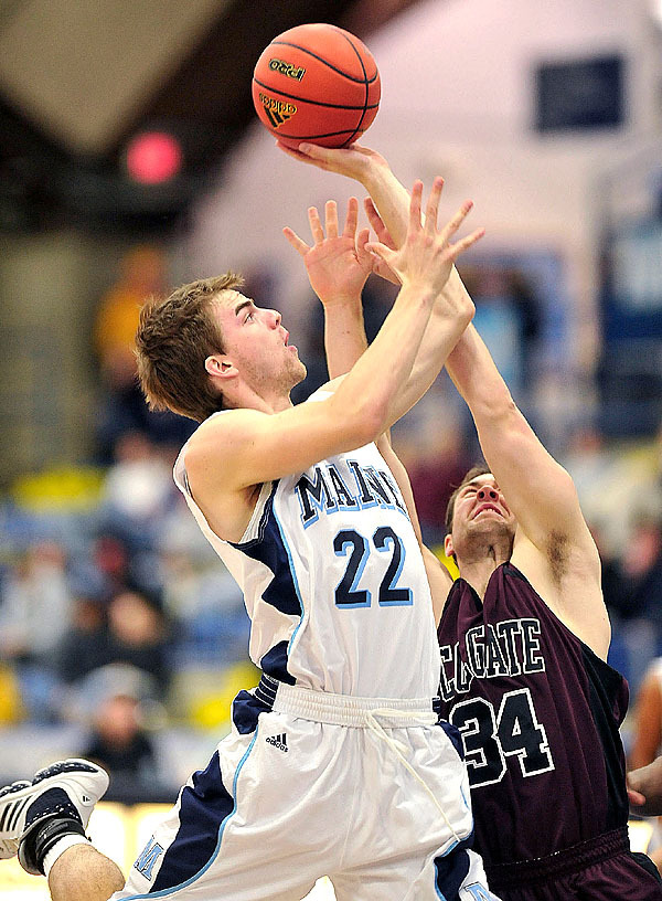 Colgate's Willie Morse, (34), tries to get two hands in the face of Maine's Mark Socoby, (22), on a drive in the first half of their game in Orono on Monday night. Buy Photo