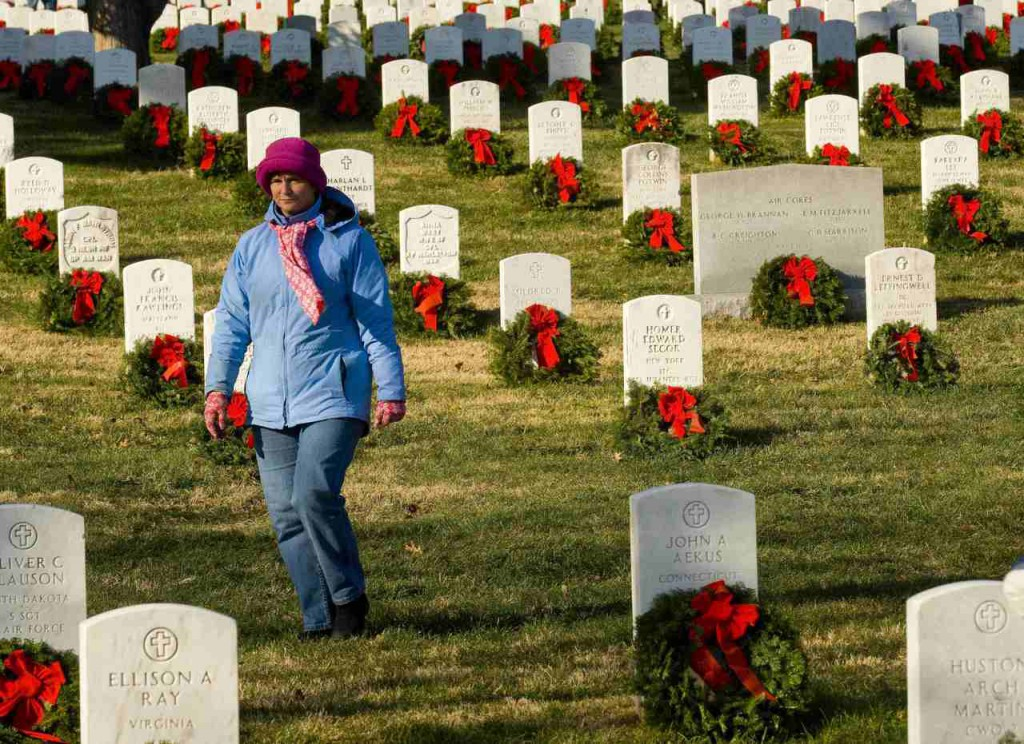Pam Hines of Edgewater, Md., walks though Section 12 of Arlington National Cemetery after she and other volunteers placed wreaths at the graves Saturday in Arlington, Va.