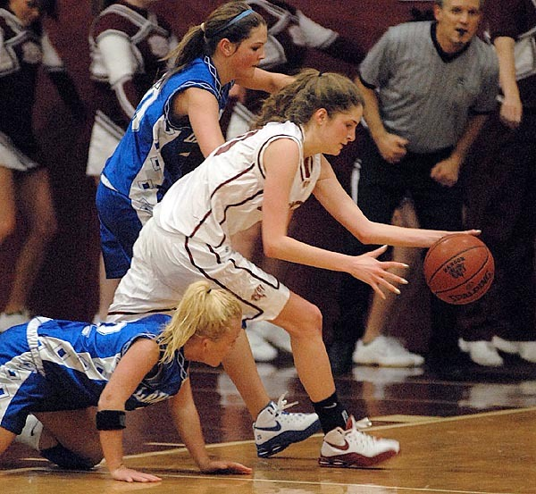 Bangor's Melanie Jackson gains control of a loose ball that she and Lawrence players Storme Savage (22) and Kristin Melcher (behind) scrambled for in first half action of Monday evening's game at Bangor High School.  Buy Photo