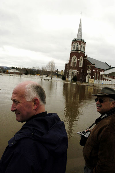In this file photo from May, Father James Nadeau (left), pastor at St. Louis Catholic Church on East Main Street, meets with Jim Somma, director of property management for the Roman Catholic Diocese of Portland, as the Fish River continues to spill into downtown Fort Kent on Wednesday.  Buy Photo