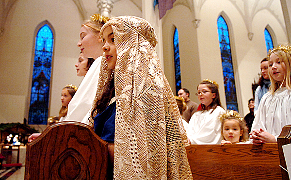 Velstara Vardamis, 8, of Bangor (center), who played the part of Mary in a Christmas pageant, participates in St. John's Catholic Church's 4 p.m. Christmas Eve Mass on Wednesday in Bangor.  Buy Photo