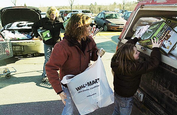 "Brownville Junction bargain hunter Kayla Goodine (center) helps her friend Sonya Goddard (left) and Goddard's daughter Lexis load Goddard's husband's truck with post-Christmas sale items after filling their car to capacity at Wal-Mart in Bangor on Friday. Goddard said she bought out the entire aisle of paper towels bearing Christmas logos. ""I'm wiping up messes, what do I care?"" she said. Buy Photo"