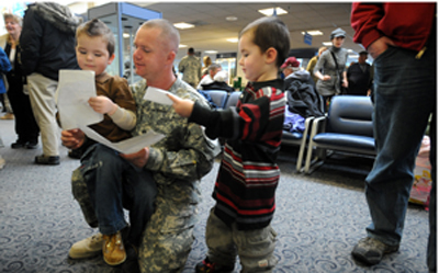 Sgt. William Sargent of Bangor looks at drawings made by his songs Brandon (left), 5, and Brady, 3, shortly after 126 soldiers of the Maine Army National Guard Medevac company landed in Bangor for a few hour stay Saturday morning. The soldiers of Charlie Company-1 16th Aviation regiment continued on to Fort Carson, Colo., for a week or so of debriefing before returning to Maine.